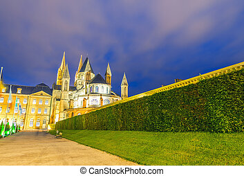 Caen. Normandy. Men Abbey exterior and gardens at night.