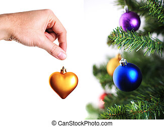 hand decorating christmas tree with gold heart - hand...