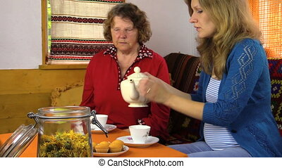 women drink marigold tea - Senior grandmother woman and...