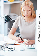 Making some business notes. Beautiful young woman writing something at her while sitting at her working place in office