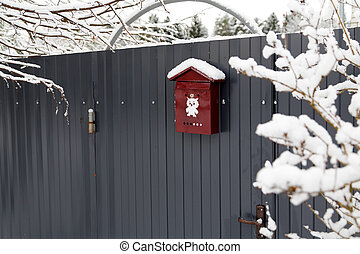 Mail box on a fence filled up by snow