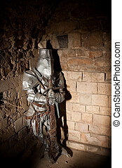 knight in armour - imprisoned medieval knight lit by a shaft...