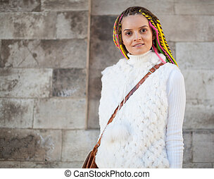 Beautiful girl with colored dreadlocks summer sunny day in a white jacket fun posing near the wall