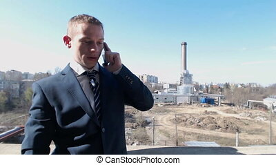 Business man talking at phone on industrial zone