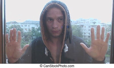 Young man stay in the rain after door