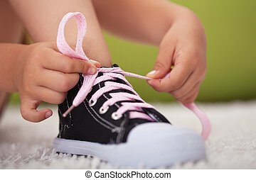 Young girl hands tie shoe laces-shallow depth of field -...