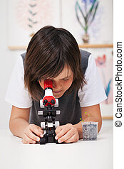 School boy in science class with microscope