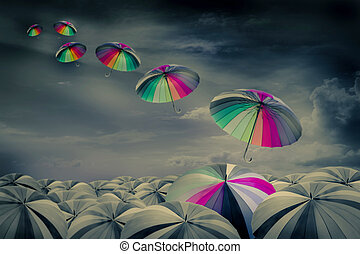 rainbow umbrella in the mass of black umbrellas