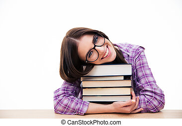 Smiling young female student sitting with books