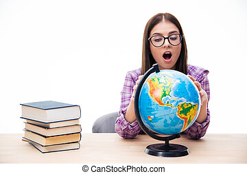 Amazed young female student looking at globe