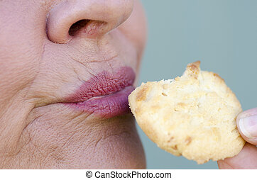 Close up woman enjoying sweet cookie - Close up image of...