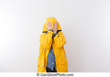 Child Wearing Yellow Rain Coat Hiding Face in Hood - Young...