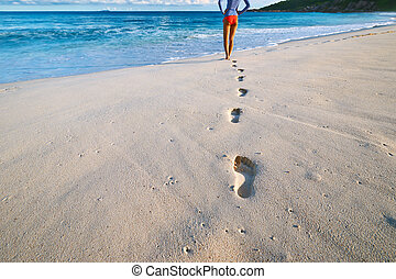 Woman at beautiful beach. Focus on footprints. - Woman at...