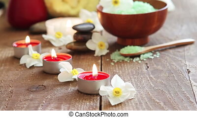 Spa still life containing bath salt, rocks, massage oil,...