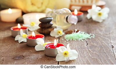 Spa still life of massage oil, towel, rocks and flowers