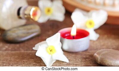 Spa still life of rocks, bath salt, massage oil and flowers