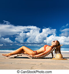 Woman in bikini lying on beach at Seychelles - Woman in...