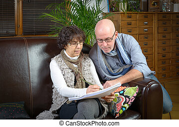 mature couple looking at a book
