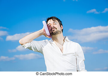 heatstroke or toothache - man holing a cold pack at his head...