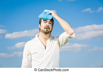 heatstroke or headache - man holing a cold pack at his head...