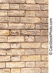 Weathered yellow brick wall vertical view