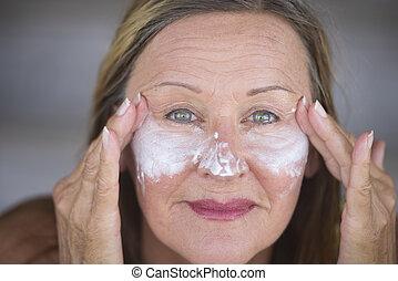 Confident mature woman face creme skin care - Portrait...