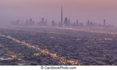 Skyline view of Dubai from night to day transition, UAE. Timelapse