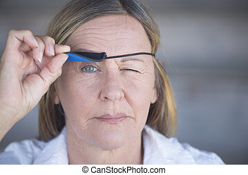 Relaxed woman lifting eye patch portrait - Portrait...