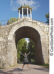 young women jump under arch in the park