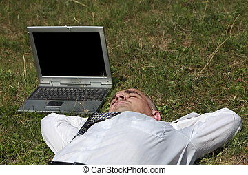 Tired man sleeping in a field near his laptop