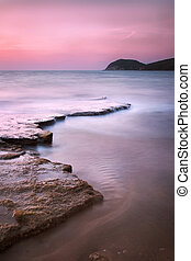 Baratti bay, headland hill, rocks and sea on sunset Tuscany,...