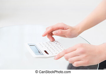 electronic calculator - Hand of a woman that uses an...