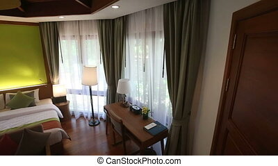 double bed hotel room with windows in curtains