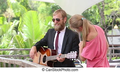 girl assistant corrects suit of bearded guitar player -...
