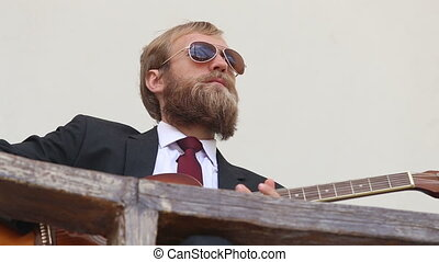 bearded man plays guitar - blonde bearded man in black suit...