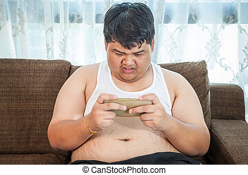 Fat asian man play game with his smartphone