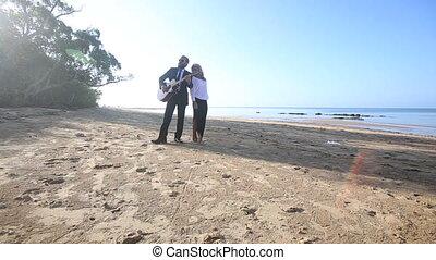 blonde guitarist plays on beach blonde girl walks around at dawn