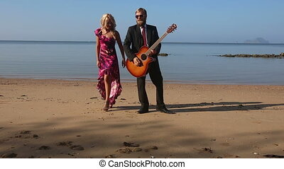 girl in red clasps to guitarist's breast on beach at dawn -...