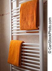 orange towels on heater in bathroom