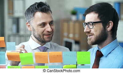 Memo Board - Two colleagues posting notes on dry erase board