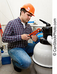 plumber installing manometer on high pressure barrel - Young...
