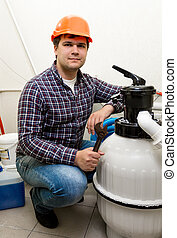 plumber posing at new pumping system with tools - Young...