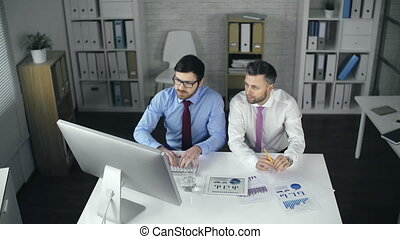 Financial Report - High angle view of two men at the desk...
