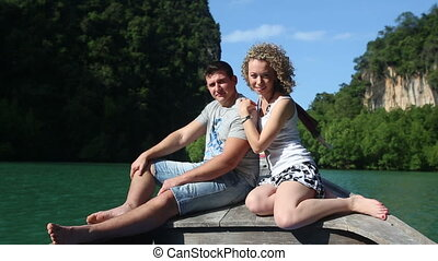 young blonde girl looks at strong handsome guy sitting on...