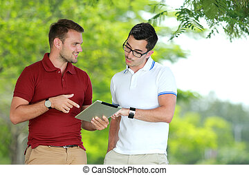 two college students discussing an assignment using tablet -...