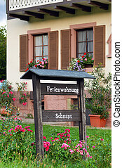 Guest house - Sign for a holiday accommodation in front of a...