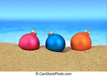 Christmas balls on sandy beach