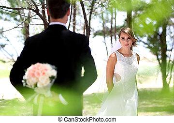 beautiful bride looking at her groom hiding something
