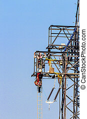 power line and electricity pylons - on a power poles work is...