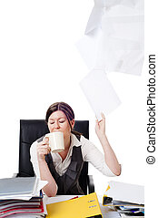 Business women at desk throwing paper up in air with cup in...